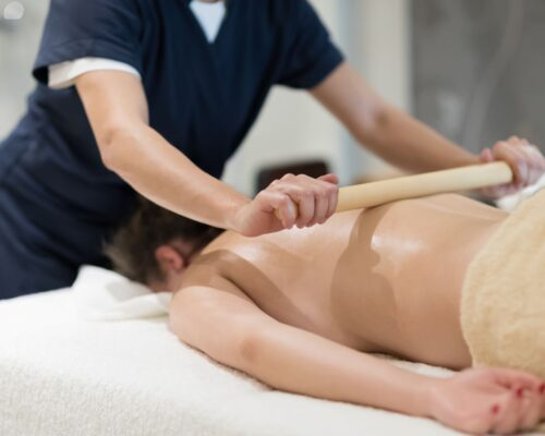 Masseur using massage bamboo sticks during treatment